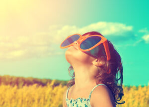 Happy little girl with big sunglasses looking at the sun in the wheat field in summer